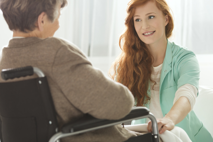 Pflegerin mit Dame im Rollstuhl