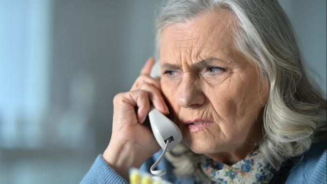 Ätere Dame hört am Telefonhörer kritisch zu